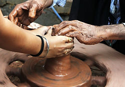 Young and old hands working pottery together