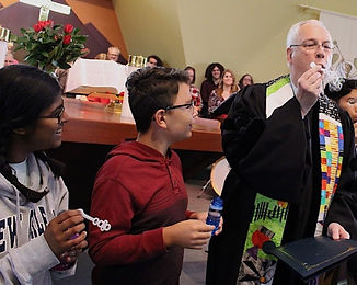 Image of a pastor and children blowing bubbles