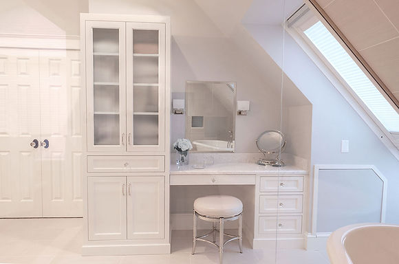 Master bathroom makeup vanity, white cabinetry with linen tower closet, glass doors, mable countertop, makeup mirror, glass knobs, soakin tub