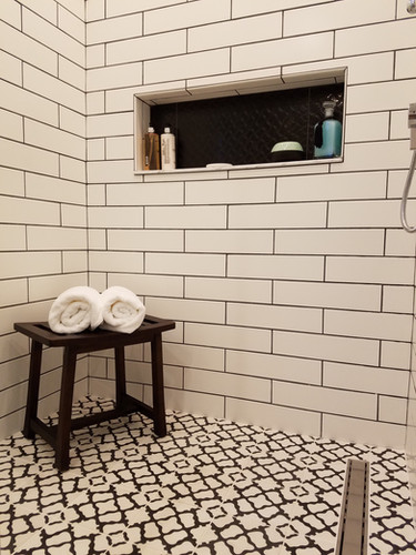 Carrying the floor tiles into the shower makes the bath feel even larger, while the oversized niche adds plenty of function