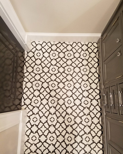 A play on classic black and white tiles in the existing bath, these cement tiles reflect the owners' unique and fun style