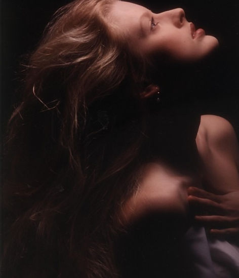 Profile shot of model with bare shoulders and flowing blonde hair, with head tilted back looking up.