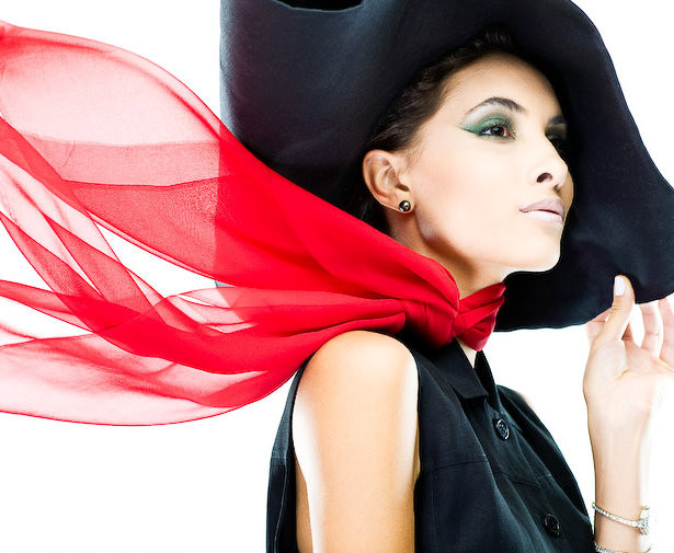 Model with large black hat and flowing red scarf. Sleeveless button up black dress. Green eyeshadow with pale pink lip color.