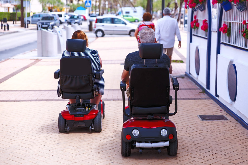 Couple%20elderly%20people%20ride%20along%20the%20sidewalk%20to%20an%20electric%20wheelchair.%20Motor