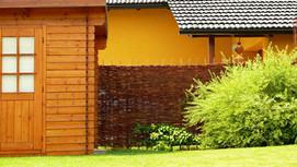 Dřevěné prvky v zahradě se s plotem z proutí od Naplot.cz krásně doplňují