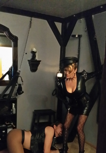 Las Vegas Dominatrix with submissive at her feet in the dungeon