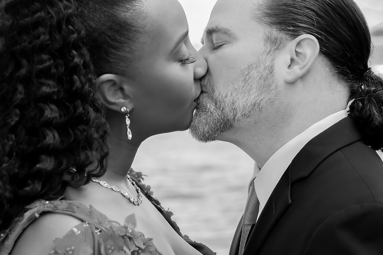 man and woman kissing in black and white