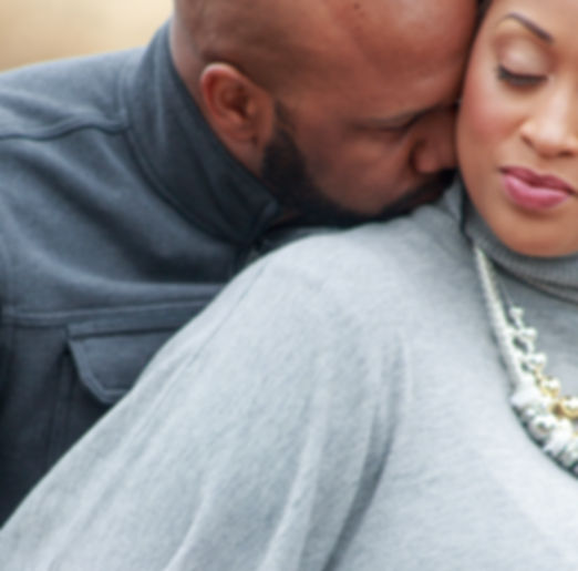 Bearded man kissing a woman at her nape.