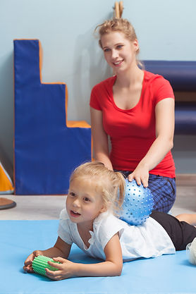 Shot of a female therapist massaging her patient's back with a ball.jpg