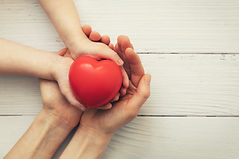 red heart in child and mother hands on white wooden background. concept of love, charity,
