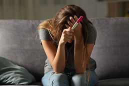 Single sad woman complaining holding a pregnancy test sitting on a couch in the living roo