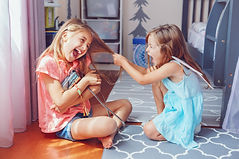 Two little mad angry girls sisters having fight at home. Friends girls can not share toy b