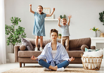 Happy mother with closed eyes meditating in lotus pose on floor trying to save inner harmo