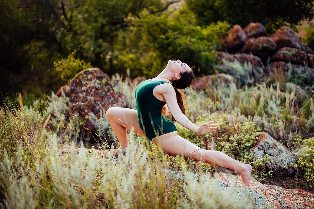 Tessa Fungo, wearing a green leotard, photographed in a lunge outdoors at Quartz Mountain. There are red rocks and green foliage surrounding the dancer.