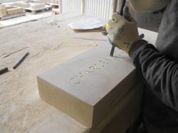 Stonemason creating name plate