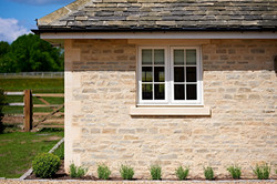 Stone quoins and heads and cills against Grange Hill Grey and Cream mix building stone