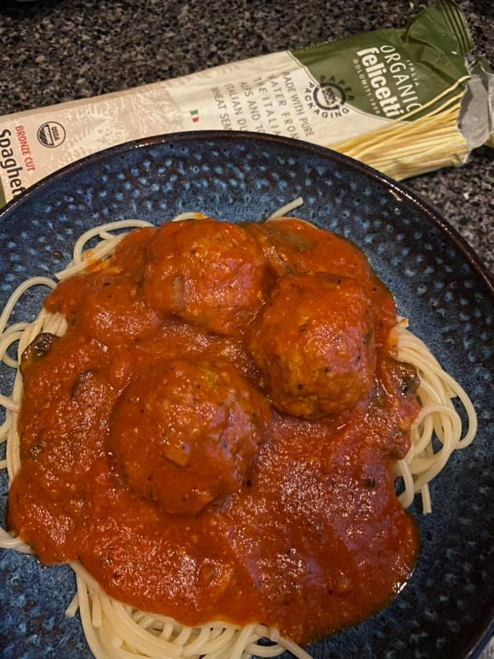 Image of three meatballs in a dish on top of spaghetti.