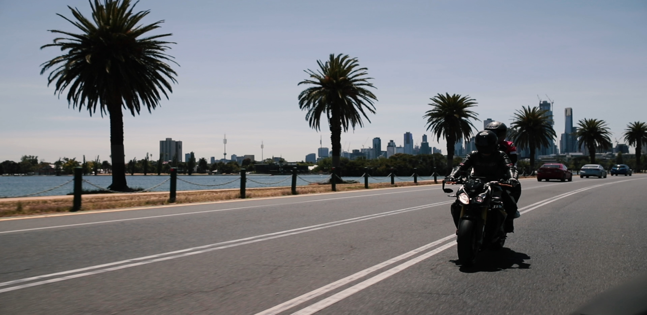 Female rider with female pillion on black BMW motorcycle riding on a road next to row of palm trees