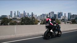 Two women on a motorcycle riding on the freeway heading into Melbourne