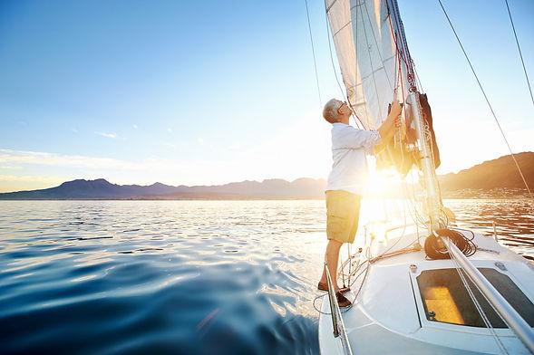 sunrise sailing man on boat in ocean wit