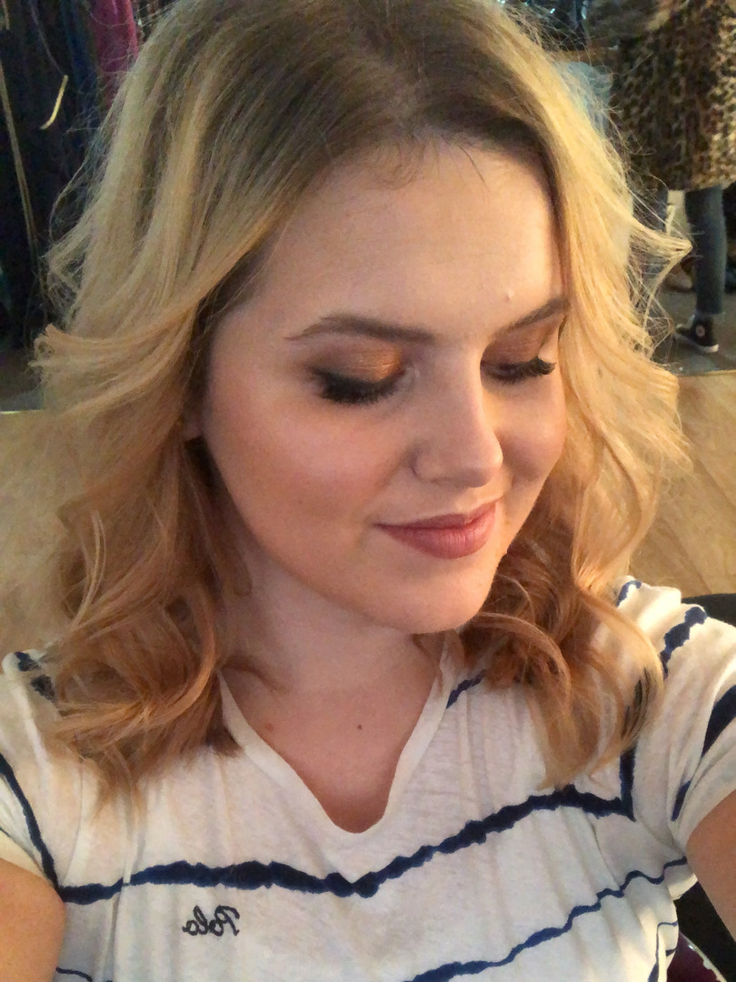 Photo of Steph gently smiling showing off her hair and makeup look at a photoshoot.