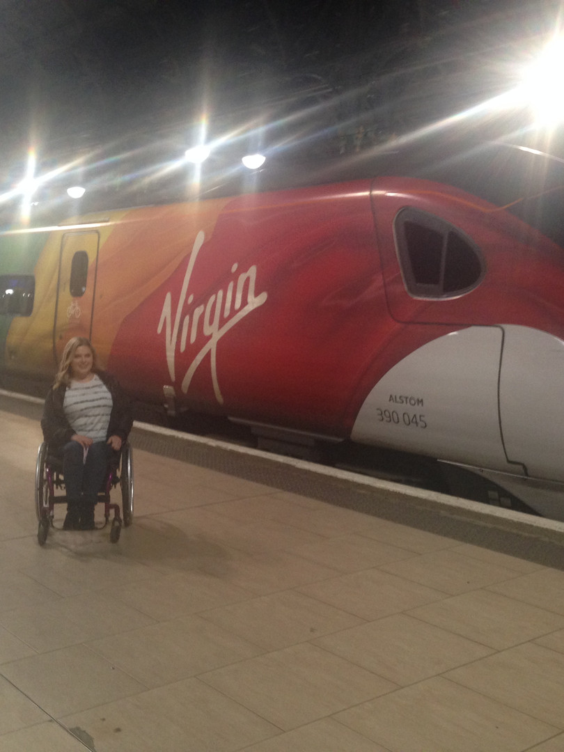 Photo of Steph in her wheelchair, slightly smiling in front of the Virgin Trains Ride With Pride Pendolino train. The train has the pride flag on it.