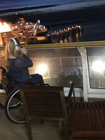 Steph is sat in her wheelchair on the outside deck on a ferry looking out to sea with headphones on.