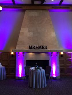 Purple uplighting behind bride/groom