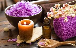 une serviette avec une bougie parfumée des fleurs et des huile essentielles