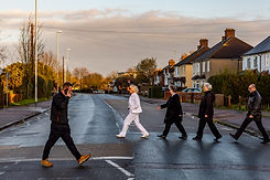 The classic Beatles Abbey Road photo parodied for a social documentary photograph being photobombed