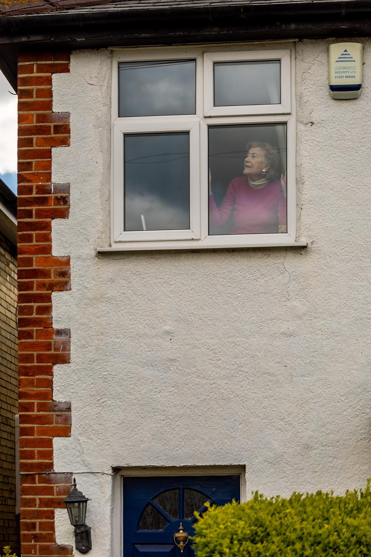 Elderly neighbour shielding gazes out of the window wistfully