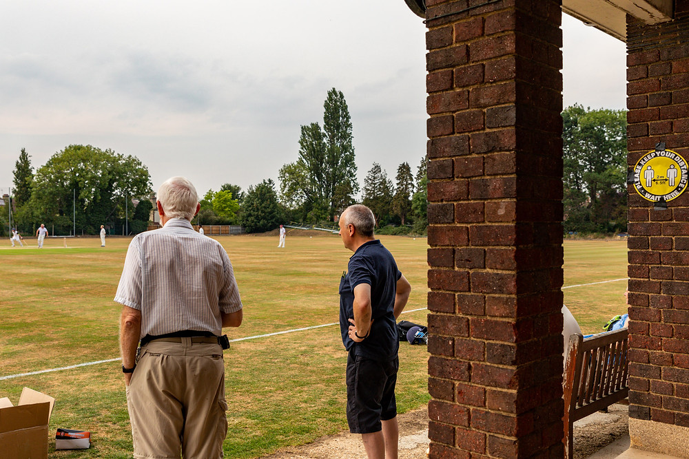 Social distancing signs for all at Fitzwilliam College Sports Ground, Cambridge University. Spectators watch teh cricket from the boundary.