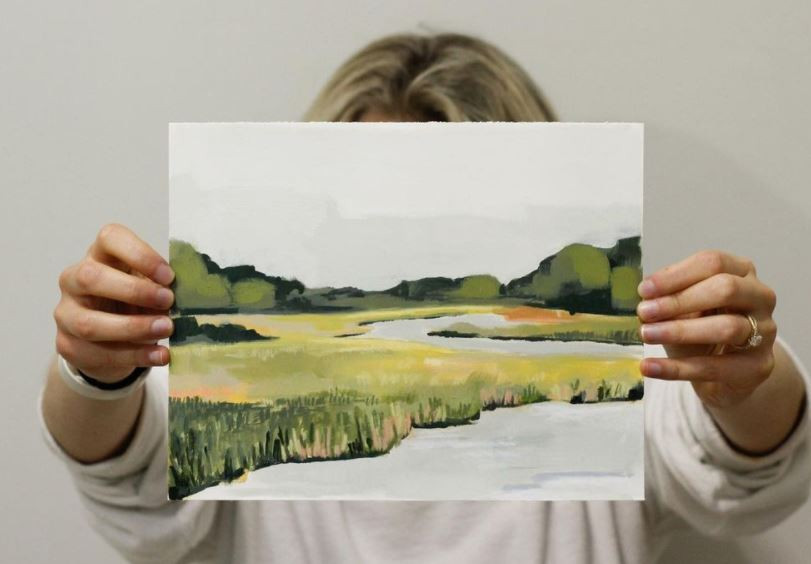 Ella holds up a painting of a soft, muted marsh with vibrant green grass and a snowy colored sky