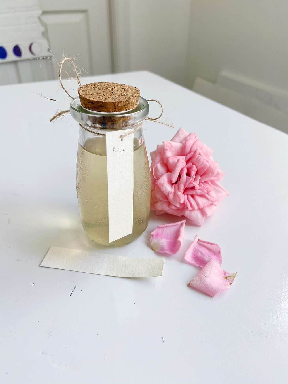 a bottle of light yellow ink with swatches and a pink rose