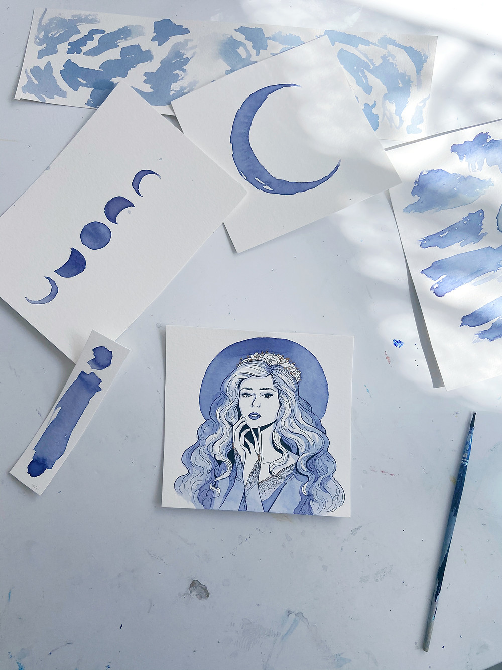 a painting of a woman using blue ink is surrounded by swatches