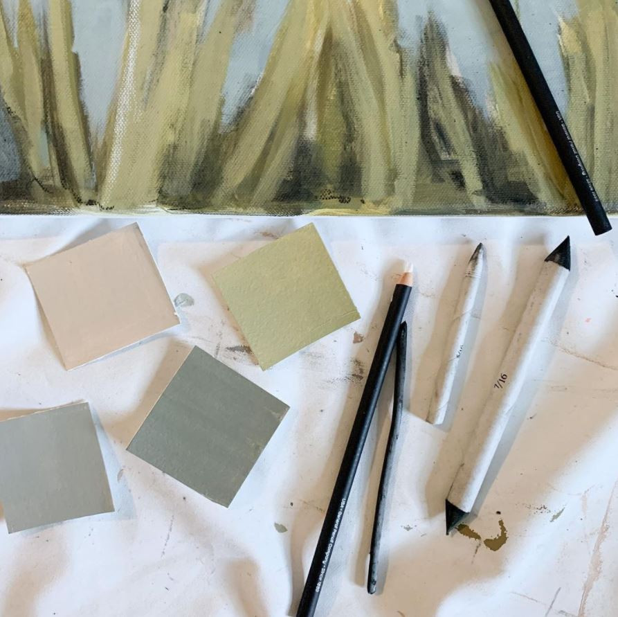 art supplies and swatches with muted greens and neutrals beside a painting