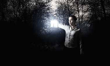 Young pretty businesswoman with lantern in darkness.jpg