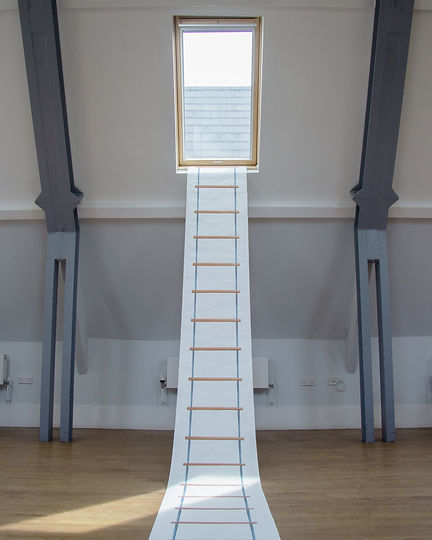 In a white loft space with wooden floor boards and grey painted wooden structure, there is a dormer window from which is displayed a long scroll of white paper with the image of a ladder – the scroll becomes a tromp l'oeil ladder