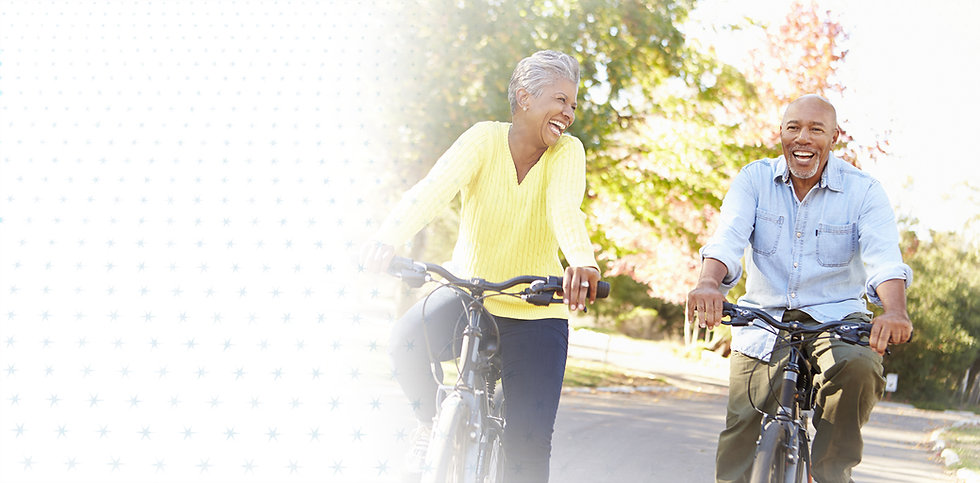 A senior couple riding bicycles and laughing