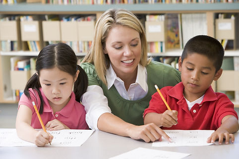 Two students in class writing with teach