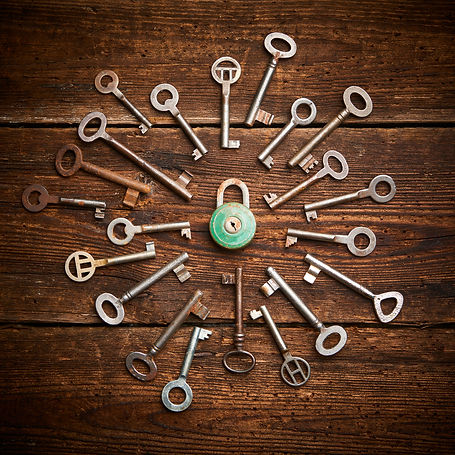 Vintage rusty padlock surrounded by group of old keys on a weathered wooden background. In