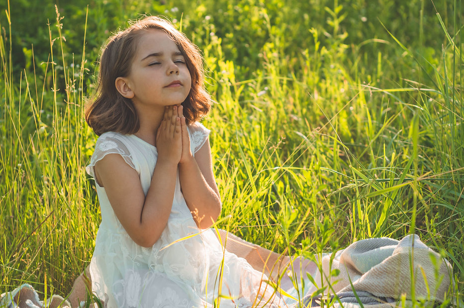 Little Girl closed her eyes, praying in a field during beautiful sunset. Hands folded in p