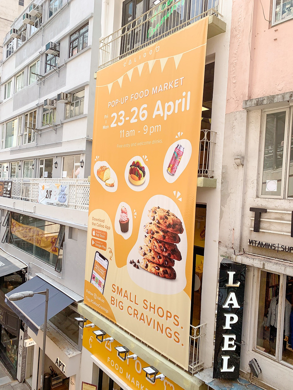 A large yellow banner of Calioo pop-up food market promoting its store in central