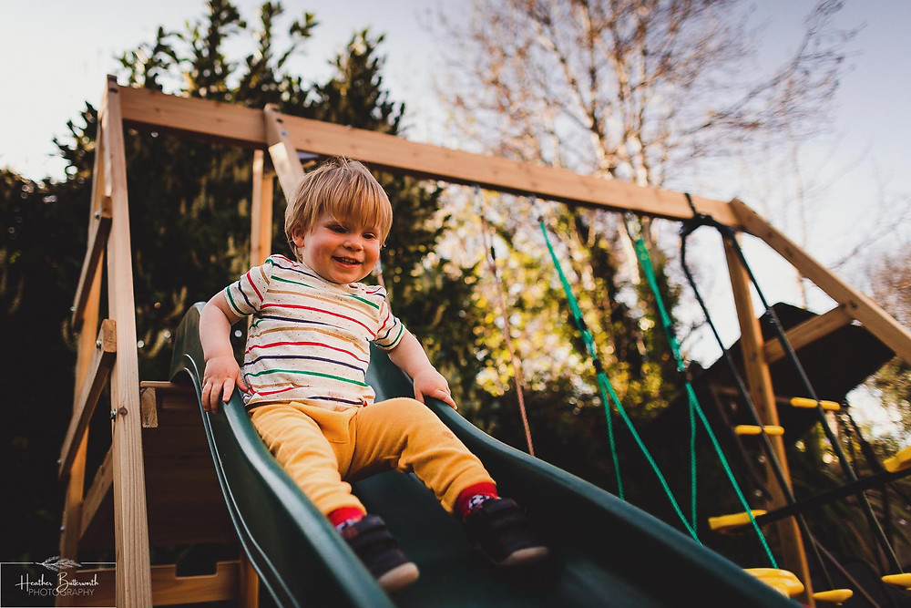 Barney going down the slide in his family garden in Leeds, Yorkshire. Image by Heather Butterworth Photography