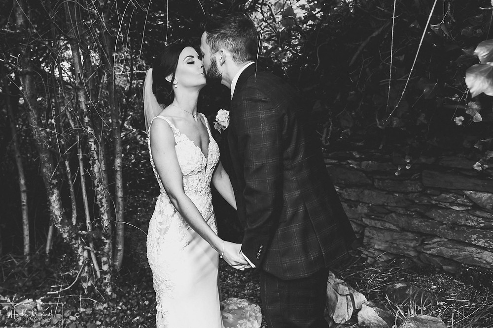 black and white image of a bride and groom kissing in the garden after their wedding at the burnside hotel and spa