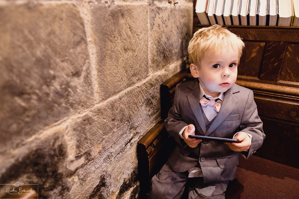 leeds wedding photographer Yorkshire adel parish church st John the baptist page boy on phone busted