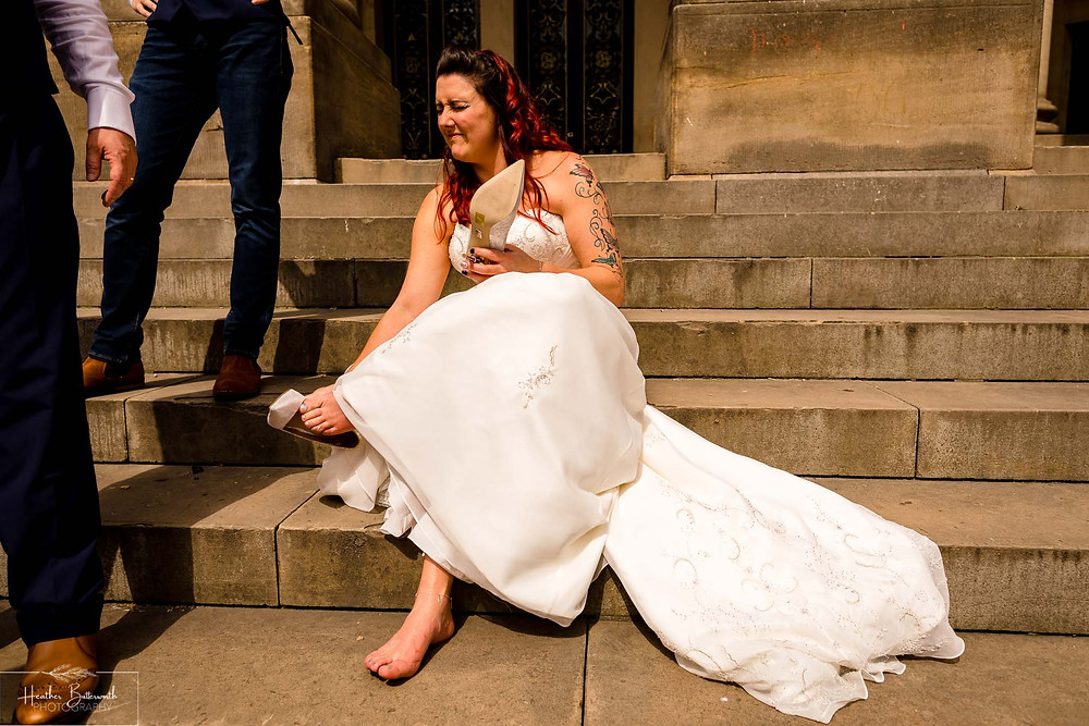 bride removing her shoes after her wedding ceremony at Leeds Town Hall in August 2020