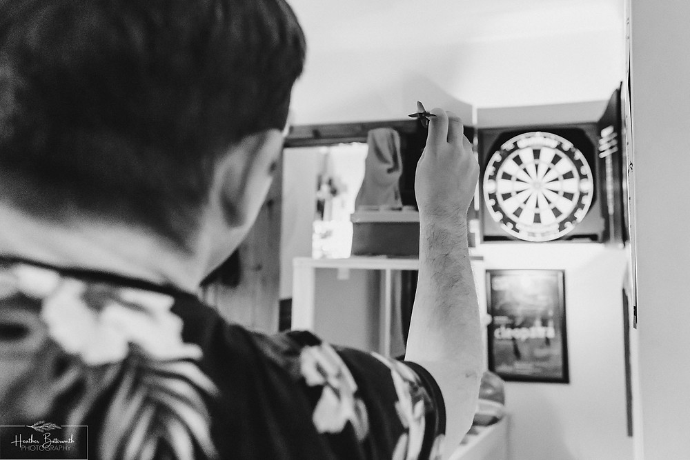 black and white image of a man throwing a dart