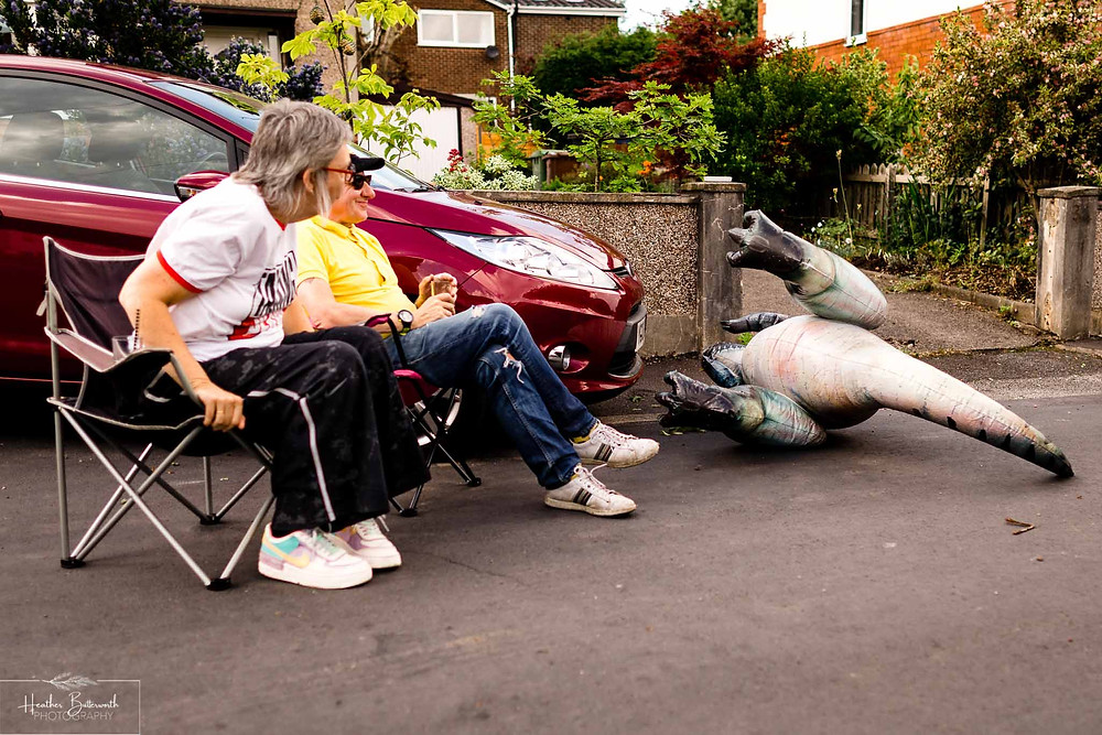 neighbours enjoying a drink in the street together with an inflatable dinosaur
