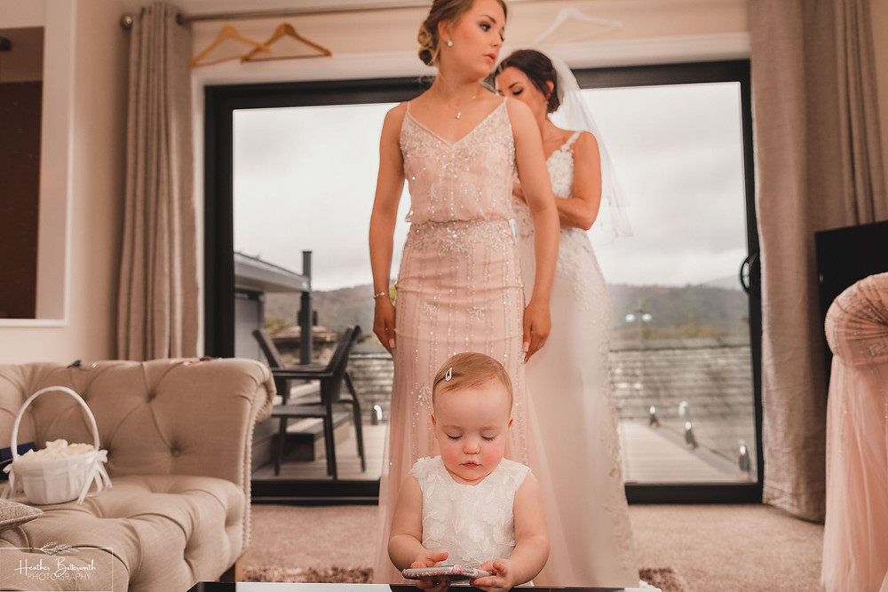 Bride Bex with her baby daughter and helping her bridesmaid with her dress stood by a window during bridal preparations at The Burnside Hotel and Spa in Bowness-on-Windermere